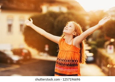Happy kid girl of 10 years old having fun outdoors wearing orange dress, dancing under the rain, arms wide open