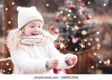Happy kid girl 4-5 year old wearing knitted hat, scarf and coat outdoors over Christmas lights holding sparklers. Winter holidays. Celebration.