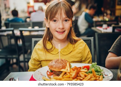 Happy kid girl eating hamburger and french fries in outdoor restaurant