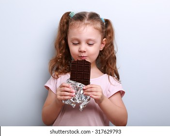 Happy kid girl eating health dark chocolate with pleasure and closed eyes on blue background with empty copy space