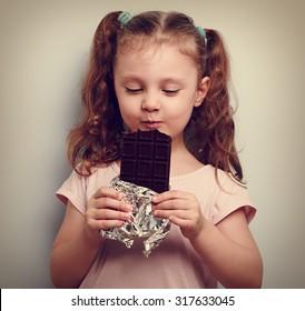 Happy kid girl eating health dark chocolate with pleasure and closed eyes. Vintage portrait