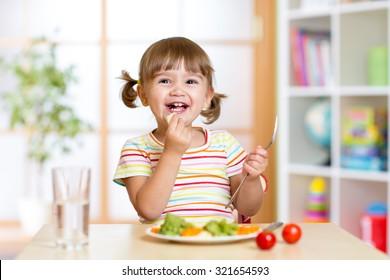 happy kid girl eating healthy food vegetables at home in nursery