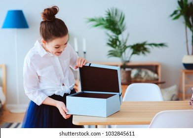 happy kid girl with gift for birthday or womans day posing at home in modern scandinavian interior, preparing or unwraping gift.