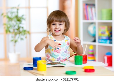 Happy kid girl with hands painted color paints sitting at table in room
