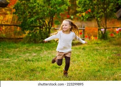 Happy kid girl having fun the autumn park.