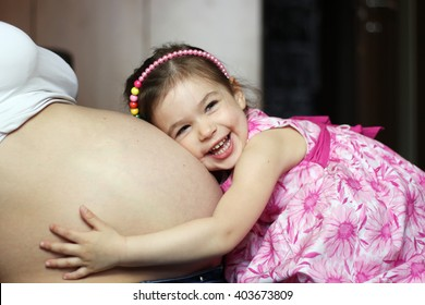 Happy kid girl hugging pregnant mother's belly, pregnancy and new life concept