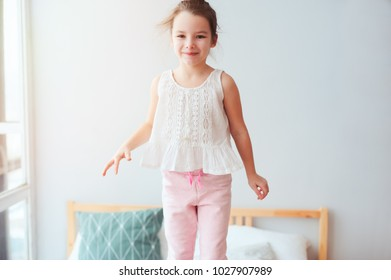 happy kid girl jumping on bed in early morning, having fun at home in weekend