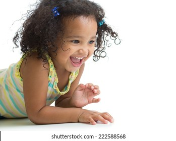 Happy kid girl lying on floor and playing isolated on white