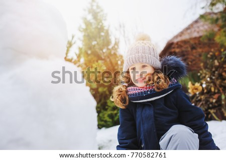 Happy Kid Girl Making Snow Man On Christmas Vacations Backyard Winter Outdoor Activities For