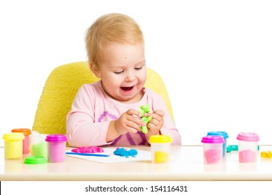 Happy kid girl playing with colorful clay toy