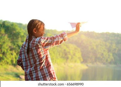 Happy kid girl playing with paper airplane at the sunset and dreaming of becoming a pilot.
