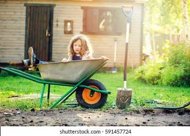 happy kid girl playing in summer garden with wheelbarrow and shovel and helping