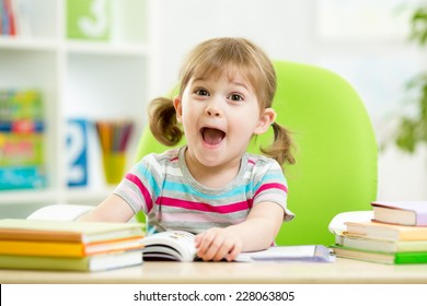 Happy kid girl reading book at table in nursery