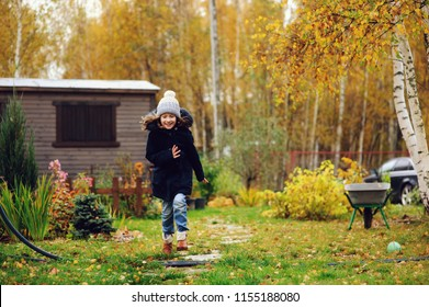 happy kid girl running in late autumn garden with wooden shed on background