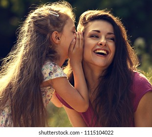 Happy kid girl whispering the secret to her laughing young mother in ear with fun face on summer green tree and grass background. Closeup toned bright portrait