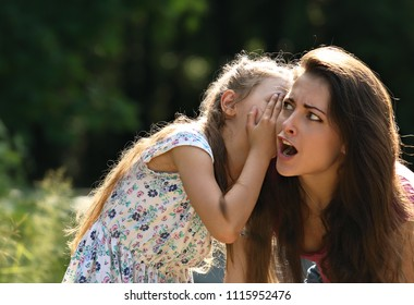 Happy kid girl whispering the secret to her surprising shocked mother with open mouth in ear with fun face on summer green tree and grass background.