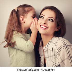Happy kid girl whispering the secret to her smiling mother in ear with fun face. Toned portrait