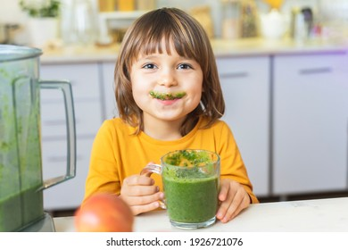 Happy Kid with glass cup of green smoothies in hands. Cute boy crazy drinks healthy dietary nutritious cocktail at home in the kitchen. Healthy lifestyle, raw food