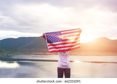 Happy kid with a hande held American flag in standing in the summer sunshine. USA celebrate 4th of July- Independence Day.
