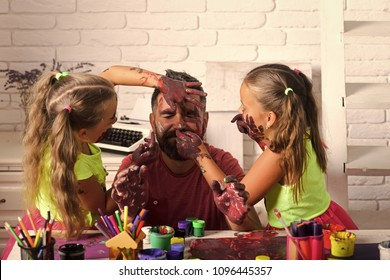 Happy kid having fun. Body art and painting. Girls drawing on man face skin with colorful paints. Fathers day and family concept. Daughters and dad smiling with painted hands. Creativity and