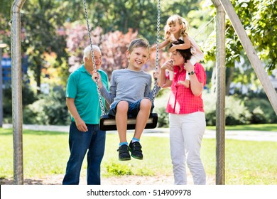 Happy Kid Having Fun On Swing With Grandparents Standing Behind In The Park