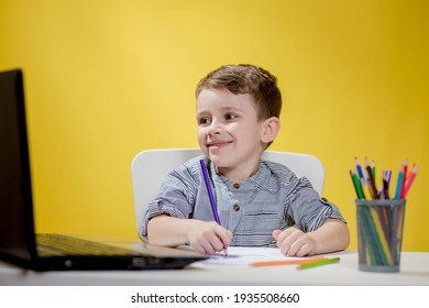 Happy kid having fun watching cartoon on laptop, Child using digital pad searching the ideas on internet for his drawing art homework, Home schooling, Social Distancing, E-learning online education.