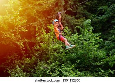 Happy kid with helmet and harness on zip line between trees