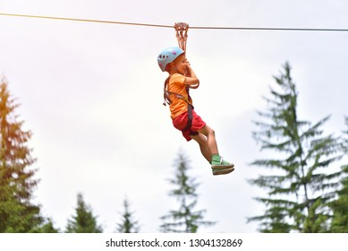 Happy kid with helmet and harness on zip line between trees