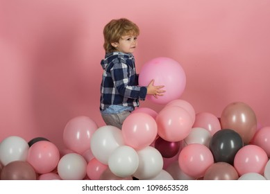 Happy kid holding pink balloons in his hand. Cute child celebrating birthday with decorations. Happy boy with holiday decorations and advertisement