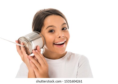 happy kid holding tin can near ear isolated on white