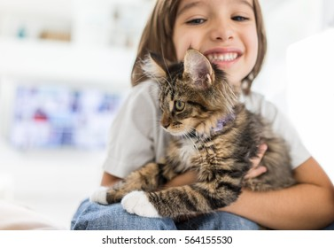 Happy kid at home playing with kitty cat