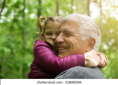 Happy kid hugging grandfather in the park. Focus on grandfather.