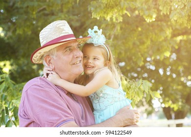 Happy kid hugging grandfather in the park.
