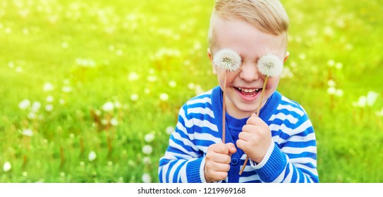 Happy kid laughing. Emotion face joy child, Close up portrait. Little boy smiling, dandelions on eyes as eyeglasses. Joyful, funny spring,summer day,outdoors.Background green grass, banner,copy space.