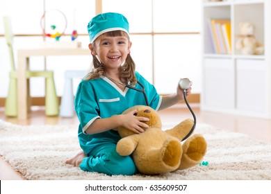 Happy kid little doctor girl examines teddy bear in nursery room at home.