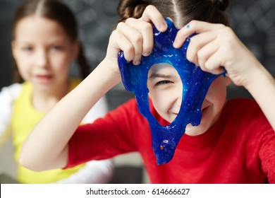 Happy kid looking through hole in blue slime
