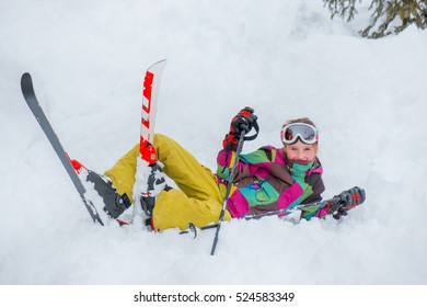 Happy kid lying with skis  in snow