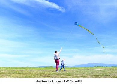 Happy kid and mom playing with kite in beautiful sunny day