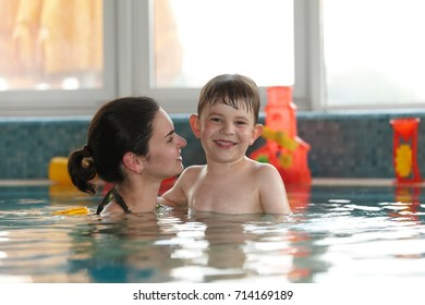 Happy kid and mother embracing in swimming pool, smiling.