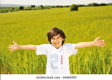 happy kid in nature, positive smiling child on green beautiful meadow with open arms looking in camera