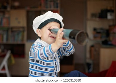 Happy kid in navy uniform looking at spy glasses through the window at home. Travel and adventure concept, young sailor dreaming