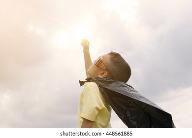 happy kid play superhero with over light of power , boy power concept