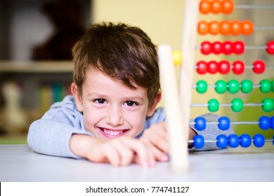 Happy kid playing with abacus toy indoors. Adorable smart child learning to count. Early kids development.