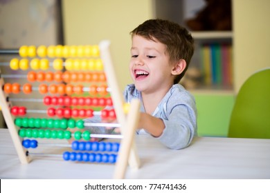 Happy kid playing with abacus toy at kindergarten. Adorable smart child learning to count. Early kids development.