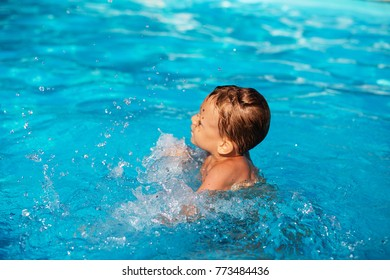 681a6fbe72 Happy kid playing in blue water of swimming pool. Little boy learning to  swim.