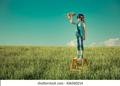 Happy kid playing. Child with toy airplane. Kid having fun outdoors. Child in summer field. Travel and vacation concept. Imagination and freedom concept