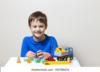 Happy kid playing with colorful plastic construction toy blocks at the table. Children, education, toys, leisure concept