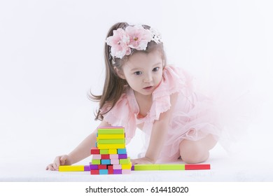 Happy kid playing her toy,puzzle,on the white background.