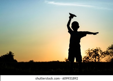 Happy kid playing with paper airplane in the sunset
