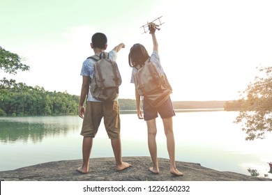 Happy kid playing toy airplane on the summer sky background. Relax time on holiday concept travel and freedom